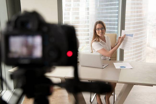 businesswoman-presenting-financial-stats-on-camera