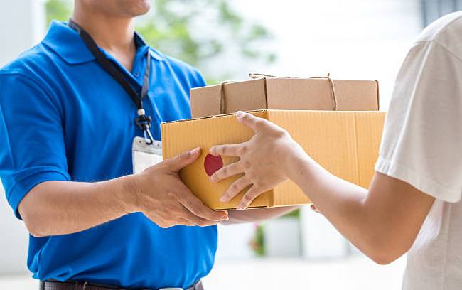 woman-hand-accepting-a-delivery-of-boxes-from-deliveryman